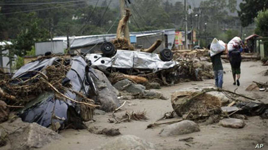Residents walk by overturned cars as they leave with their belongings after a landslide in Teresopolis, Brazil, 13 Jan 2011
