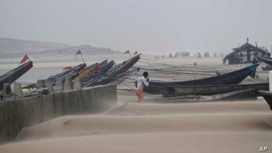 An Indian fisherman walks near the anchored fishing boats as strong winds blow a day after a powerful cyclone pounded the Bay of Bengal coast in Gopalpur, Orissa, about 285 kilometers (178 miles) north east of Visakhapatnam, India, Monday, Oct. 13, 2