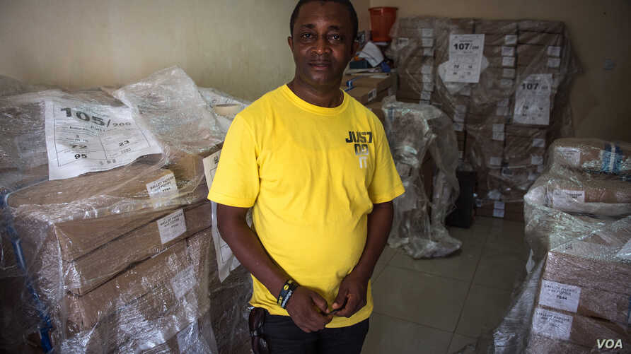 Andrew Raka, electoral officer in charge of Port Loko district, stands in front of some of the ballots which will be used during the election in Port Loko, Sierra Leone, March 10, 2018. (J. Patinkin/VOA)