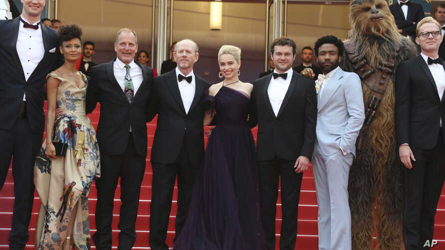 Actors Joonas Suotamo, from left, Thandie Newton, Woody Harrelson, director Ron Howard, actress Emilia Clarke, actor Alden Ehrenreich, actor Donald Glover, a person dressed as the character Chewbacca and actor Paul Bettany pose for photographers upon