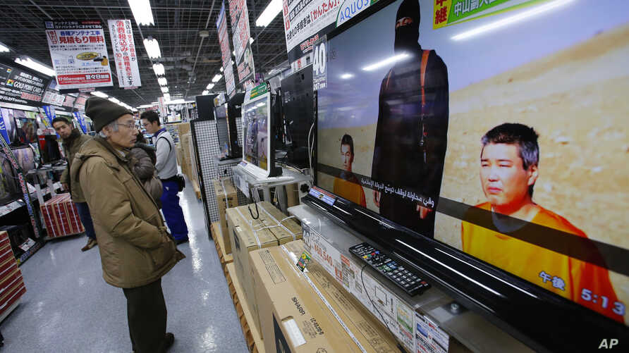 A man watches a television broadcasting a news about detained two Japanese, at an electronics store in Tokyo, Tuesday, Jan. 20, 2015.