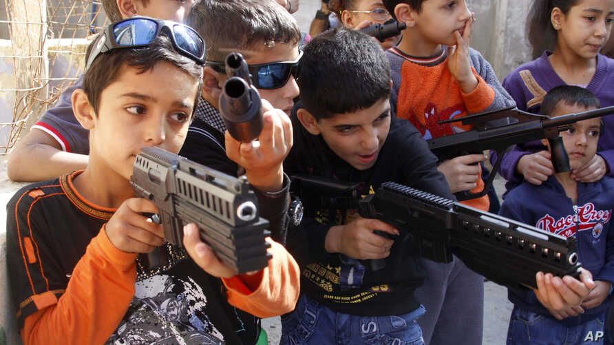 Syrian refugee children play with toy weapons as they imitate Syrian rebels and Syrian troops at a refugee camp in the southern port city of Sidon, Lebanon, Saturday, Oct. 27, 2012.  Refugee children often act out their trauma through play.