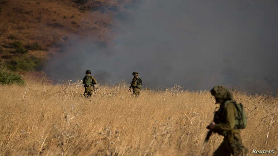 Israeli soldiers patrol next to a smoke from a fire caused by a rocket attack in northern Israel, near the Lebanese border, Aug. 20, 2015.