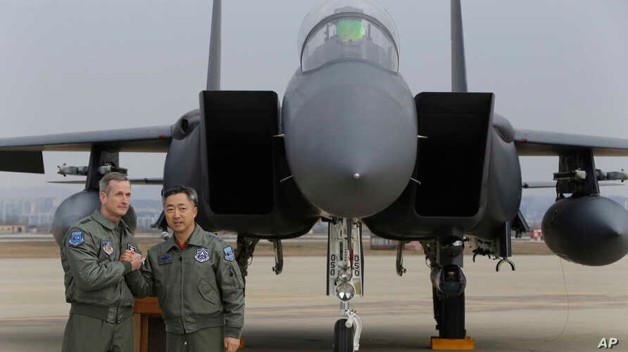 Lt. Gen. Terrence O'Shaughnessy, left, 7th Air Force commander of the U.S. Forces to Korea, and South Korean Air Forces Commander Lee Wang-geun pose in front of a South Korean F-15K fighter jet after a press briefing on the flight by a U.S. Air Force