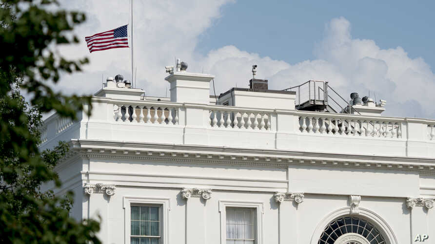 The American flag files at half-staff at the White House, Monday afternoon, Aug. 27, 2018, in Washington.