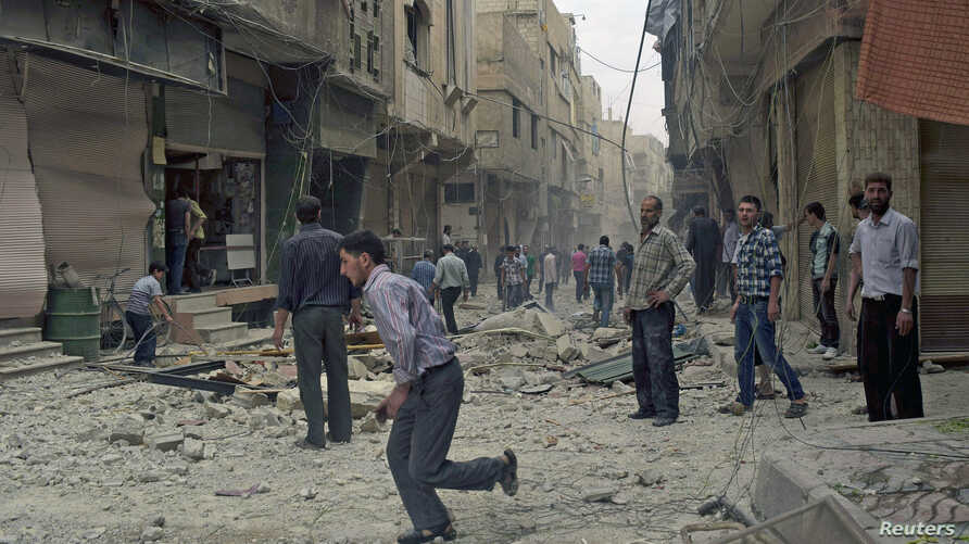 Residents stand at a site hit by what activists said were airstrikes by forces loyal to Syria's President Bashar al-Assad in Arbeen town, outside Damascus, May 27, 2015.
