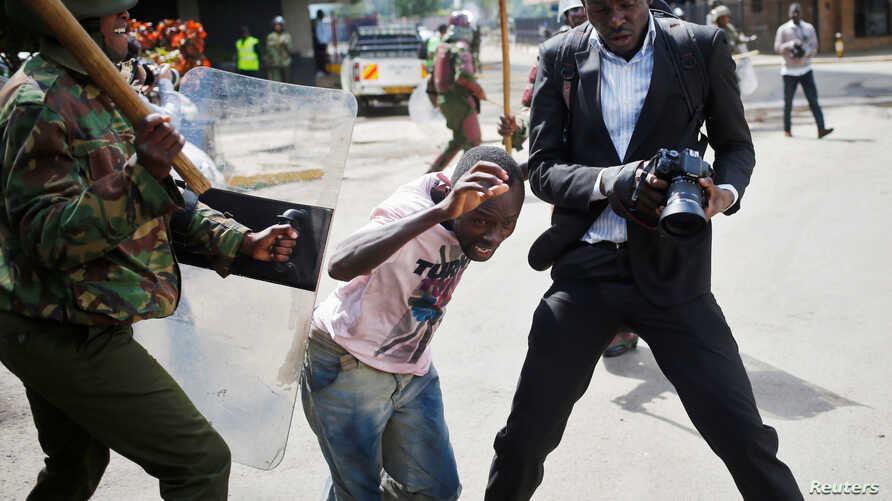 A Kenyan policeman beats a protester during clashes in Nairobi, May 16, 2016.