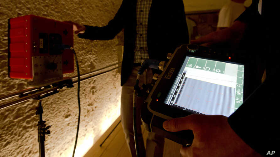FILE - Radar scanning experts scan a wall at King Tutankhamun's burial chamber at his tomb at the Valley of the Kings in Luxor, Egypt, April 1, 2016.