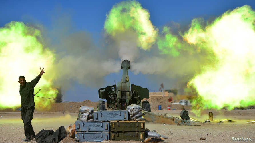 Popular Mobilization Forces (PMF) fire toward Islamic State militants during a battle with west of Mosul, Iraq,  Feb. 22, 2017.
