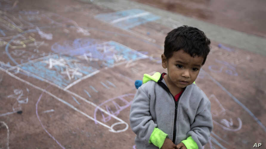 A child stands on a pavement adorned with chalk drawings at the El Chaparral U.S.-Mexico border crossing, in Tijuana, Mexico, May 2, 2018,