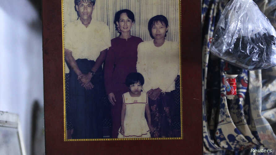 A family photograph of slain journalist Par Gyi, his wife Than Dar and their daughter posing with Aung San Suu Kyi is shown at their home, in Yangon, Myanmar, Oct. 28, 2014.