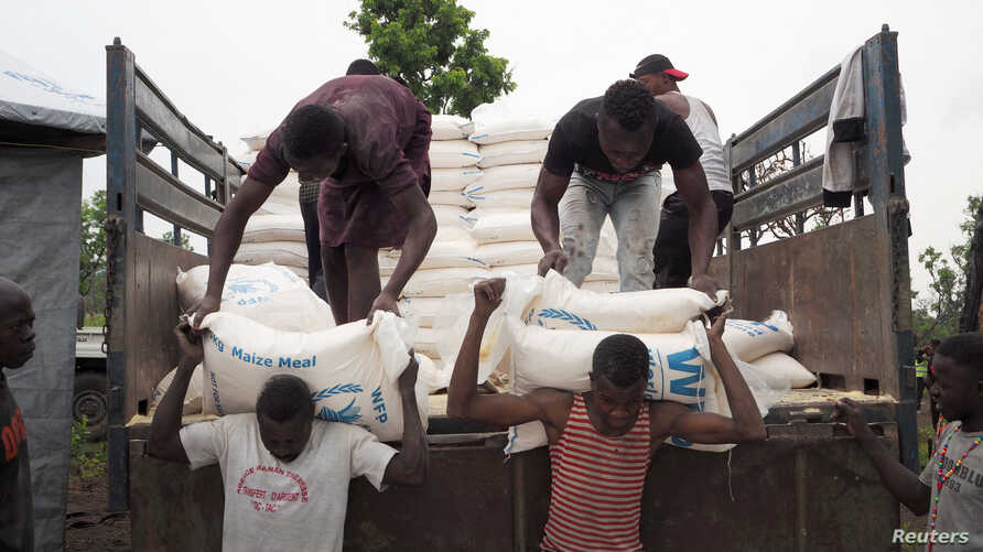 Volunteers unload maize meal supplied by the United Nations Food Program at the Lovua refugee camp in Angola, Sept. 13, 2017. More than 6,000 Congolese have fled to Zambia in the last month.