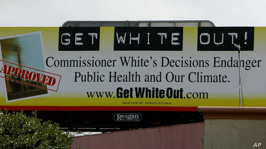 FILE - A sign near the headquarters of the Texas Commission on Environmental Quality, July 17, 2007, in Austin, Texas, calls for the removal of chairwoman Kathleen Hartnett White. The watchdog group Public Citizen says it is targeting White because o