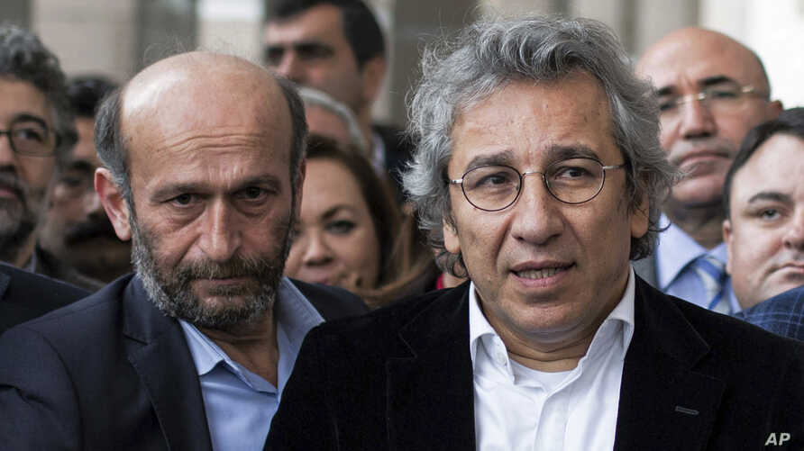 Can Dundar, right, the editor-in-chief of opposition newspaper Cumhuriyet, and Erdem Gul, left, the paper's Ankara representative, speak to the media outside a courthouse in Istanbul, Turkey, Nov. 26, 2015.