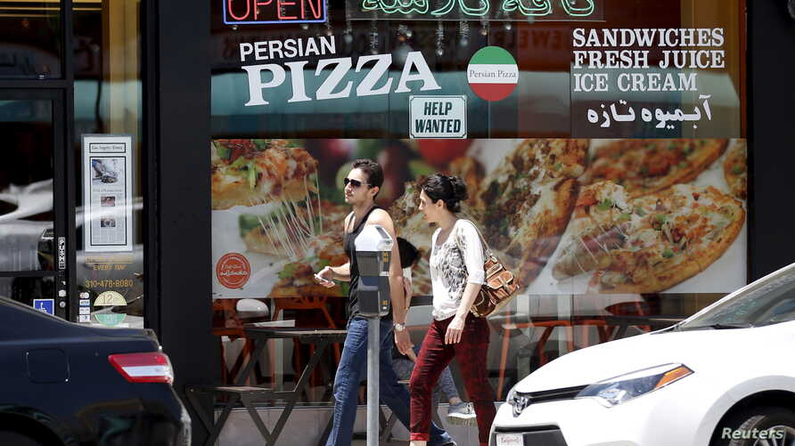 FILE - A couple walks past a Persian pizza restaurant near Persian Square in Westwood, Los Angeles.