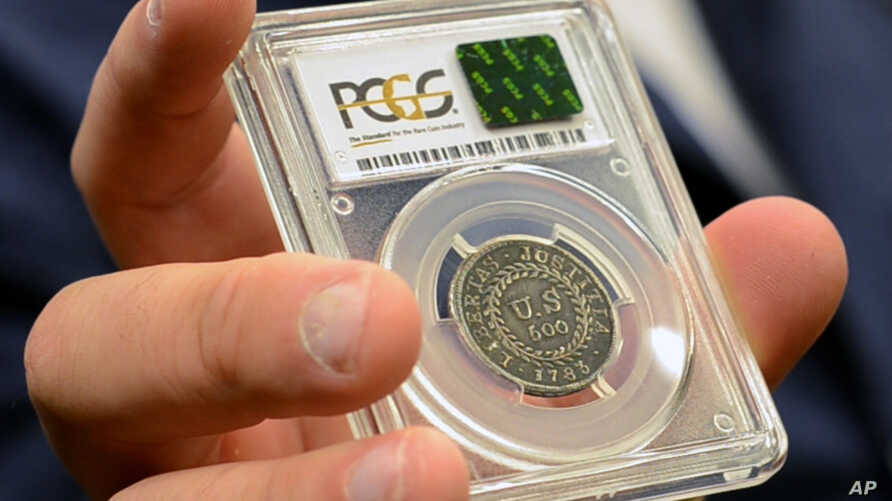 In this July 31, 2017, image made from a video, David McCarthy, a senior numismatist at Kagin's, holds what is believed to be the first coin ever struck by the U.S. government at the World's Fair of Money in Denver, Colorado.