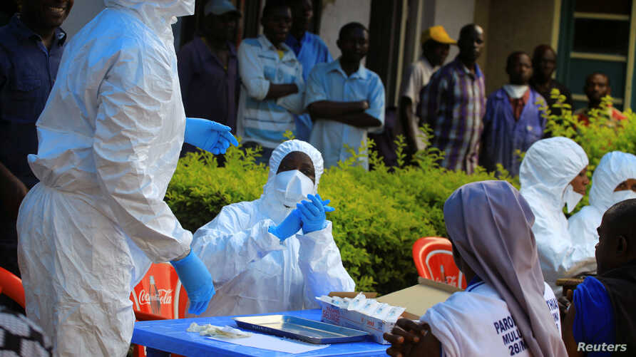 Congolese and WHO officials wear protective suits as they prepare equipment before the launch of vaccination campaign against the deadly Ebola virus near Mangina village, near Beni in North Kivu province, DRC, Aug. 8, 2018.