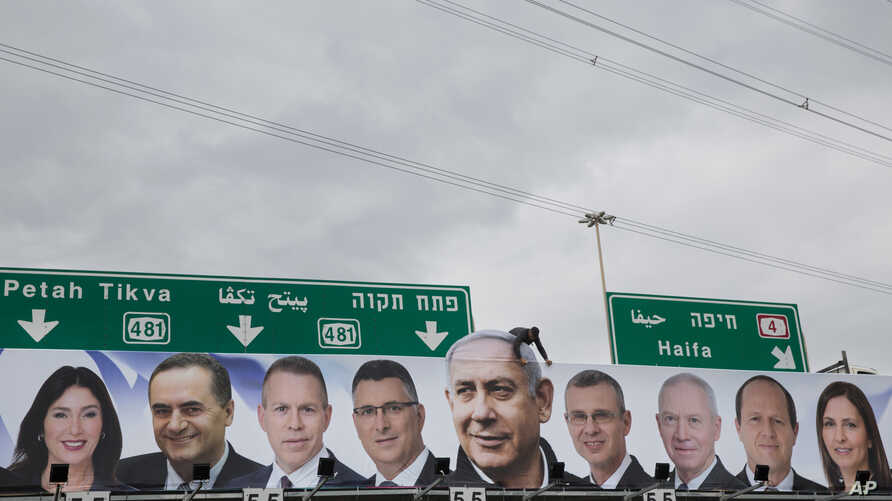 A man works on a Likud party election campaign billboard depicting Israeli Prime Minister Benjamin Netanyahu, center, and his party candidates, in Petah Tikva, April 1, 2019.