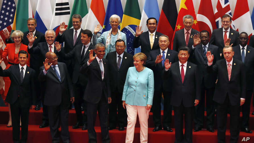 U.S. President Barack Obama, front row third from left, Chinese President Xi Jinping, second from right, and other leaders wave as they pose for a group photo session for the G-20 Summit held at the Hangzhou International Expo Center in Hangzhou in e