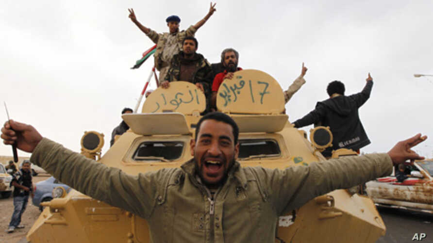 Libyan rebels celebrate on a armored personnel carrier in the strategic oil town of Ajdabiyah, March 29, 201