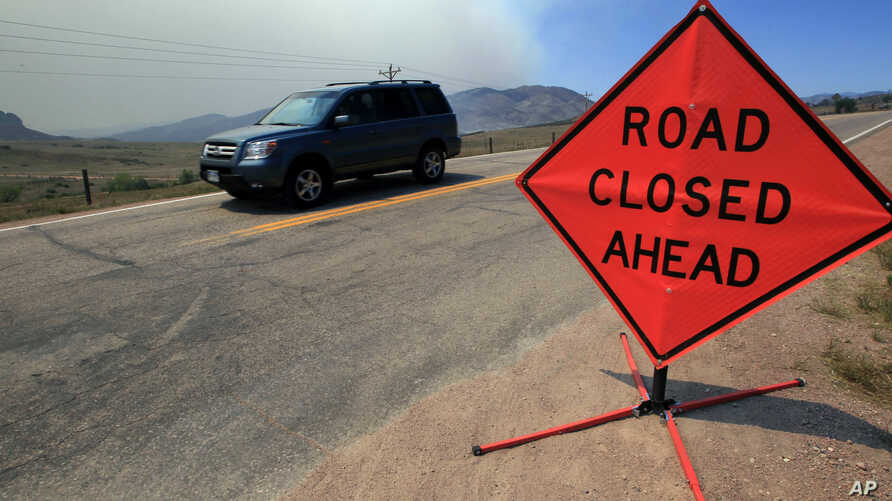 File - Smoke rises in the background as a motorist drives down Larimer County Highway 74W as a wildfire burns, near Livermore, Colorado.
