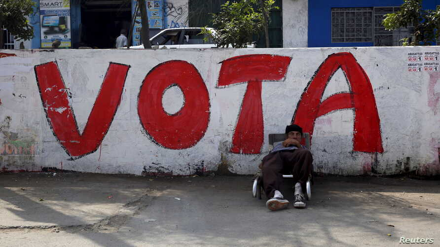 A man rests near a sign that reads 'vote' on a street in Comas on the outskirts of Lima, Peru, March 4, 2016.