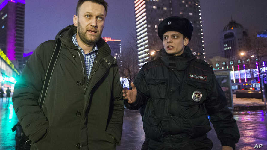 Russian opposition activist and anti-corruption crusader Alexei Navalny (l) is detained by police after defying his house arrest to speak on Radio Echo Moskvy in Moscow, Jan. 14, 2015.