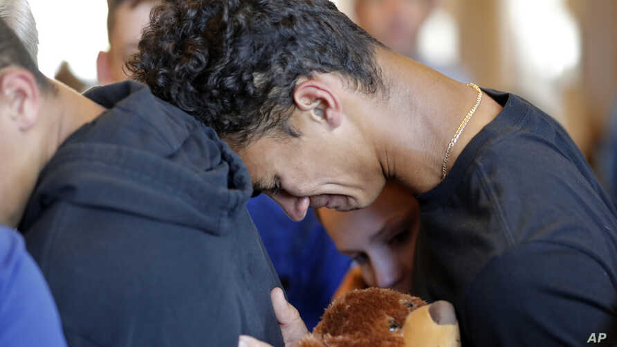Austin Burden, 17, cries on the shoulder of a friend after a vigil at the Parkland Baptist Church, for the victims of the Wednesday shooting at Marjory Stoneman Douglas High School, in Parkland, Fla., Feb. 15, 2018.