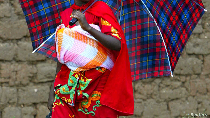 FILE - A young woman covers her baby from the hot sun in Burundi's capital, Bujumbura.