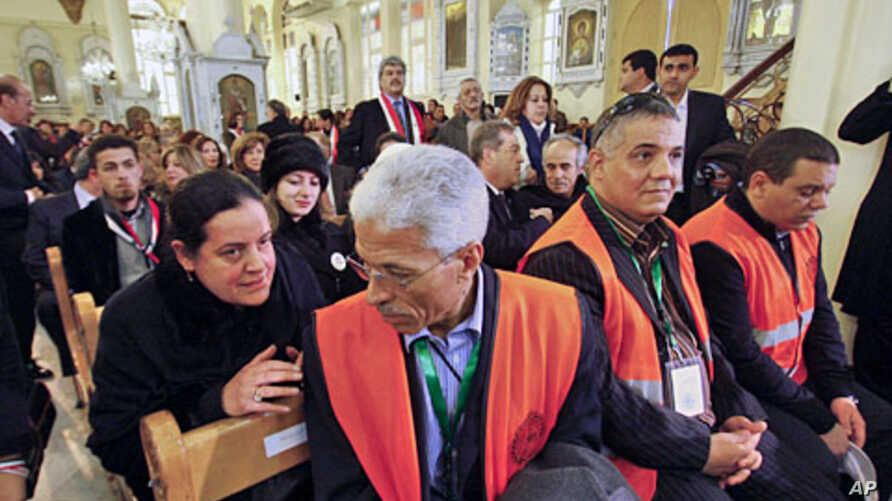 A Syrian woman (L) speaks with an Arab league observer,  (R) who attends with other observers a mass prayer for the people and army soldiers who were killed during the violence around the country, at the Holy Cross Church, in Damascus, January 9, 201