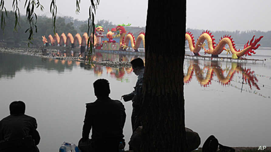 Chinese security guards rest near a giant dragon shaped lantern set up to mark mid-autumn festival in Beijing, China, September 12, 2011.