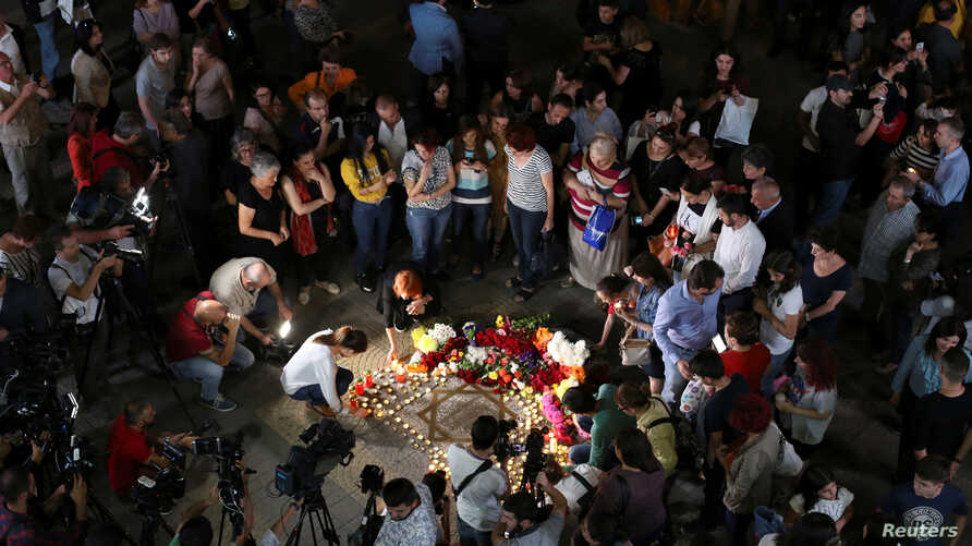 People bring flowers and candles during a gathering in memory of singer Charles Aznavour, who died aged 94, in Charles Aznavour Square in Yerevan, Armenia, Oct. 1, 2018.
