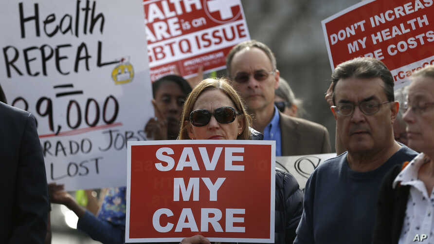 FILE - Supporters of the Affordable Care Act, who are also opponents of Colorado's GOP-led plan to undo Colorado's state-run insurance exchange gather for a rally organized by the national Save My Care Bus Tour, on the state Capitol steps in Denver,