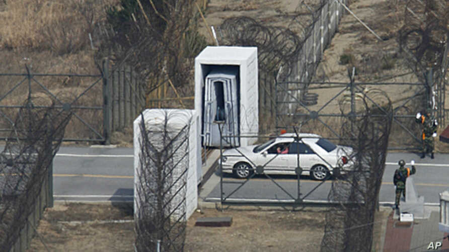 A South Korean tourist in his own car enters the Demilitarized Zone (DMZ) to cross border separating the two Koreas in Goseong, far northeast of South Korea as soldiers wave, March 17, 2008
