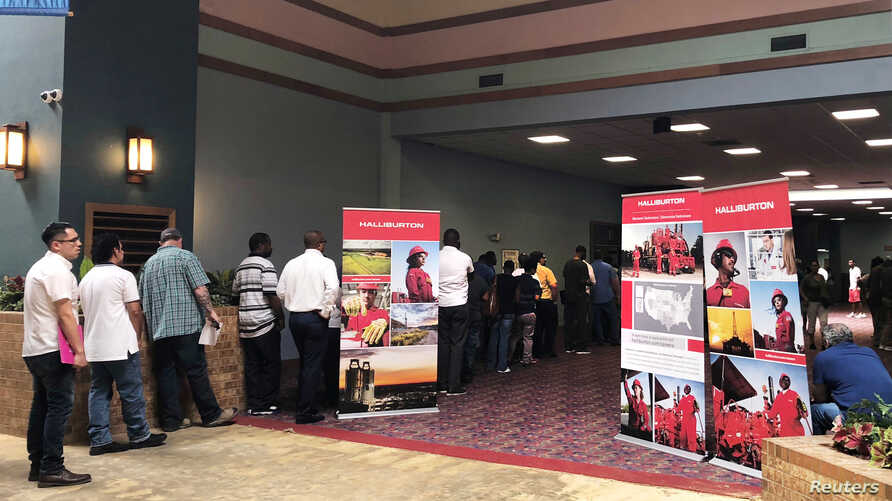 Job seekers line up at a job fair of an oil services giant Halliburton at the MCM Grande Fundome hotel in Odessa, Texas, July 19, 2018.