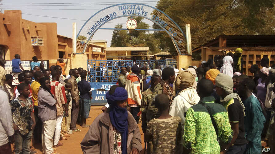 People gather outside a hospital were injured were taken after a suicide bomber in an explosives-laden vehicle attacked  the Joint Operational Mechanism base in Gao, Mali, Jan. 18, 2017.