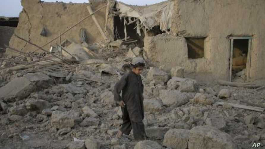 A boy walks past a mud house damaged by a bomb explosion early morning in the Pakistan-Afghanistan border town of Chaman, July 14, 2011