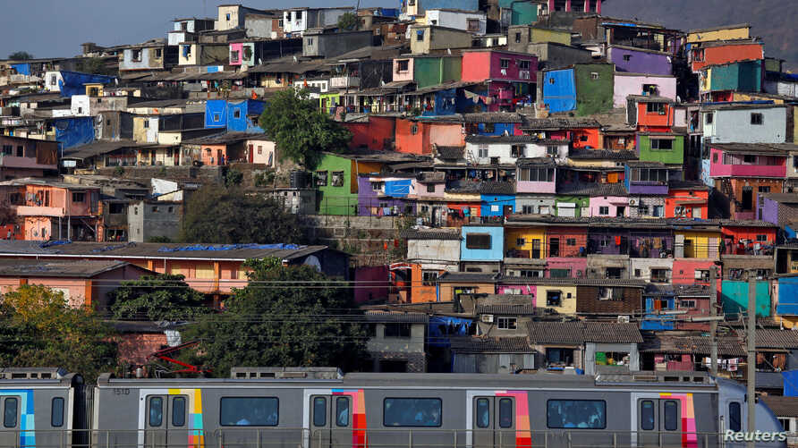 A metro train moves past a cluster of houses at the Asalpha slum in Mumbai, India, April 12, 2018.