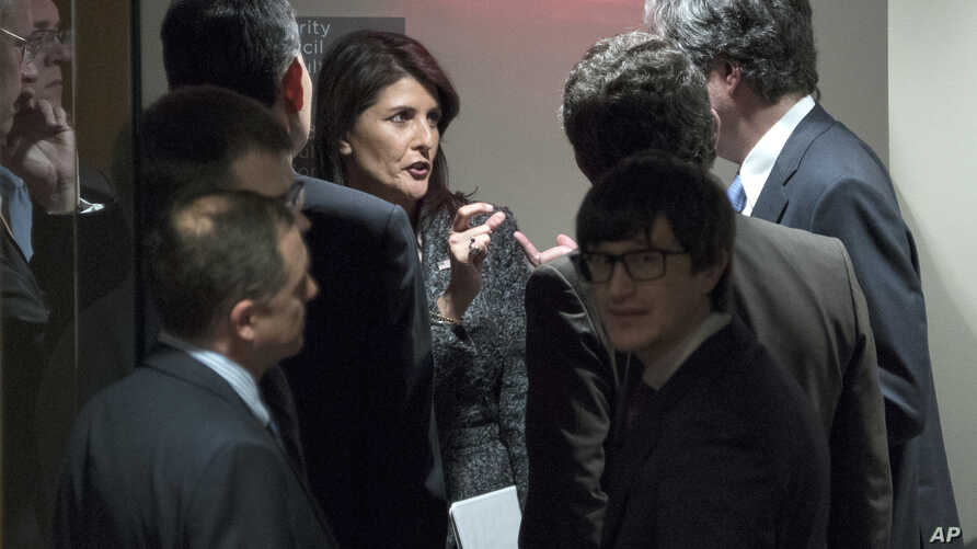 U.S. Ambassador to the United Nations Nikki Haley, center, confers with members of the Security Council just outside the chamber before a scheduled vote on a resolution demanding a 30-day humanitarian cease-fire across Syria, Feb. 24, 2018.