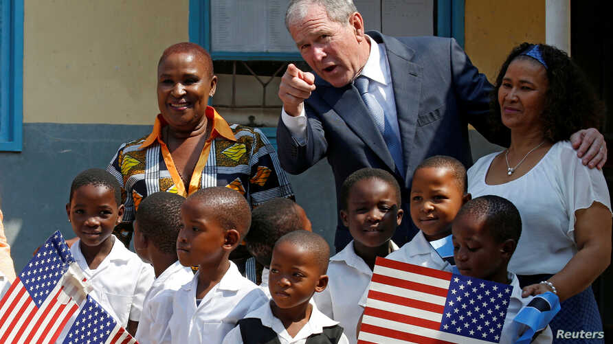 Former US President George W. Bush greets children at a school in Gaborone, Botswana, April 4, 2017.