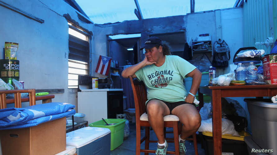 Jazmin Morales sits in her kitchen without power and with a plastic sheet replacing the roof after Hurricane Maria hit the island in September, in Yabucoa, Puerto Rico, Jan. 29, 2018.