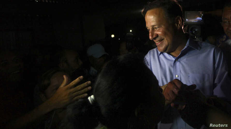 Juan Carlos Varela of the Panamenista Party (PP) shakes hands with supporters during his first public presentation as the elected president of Panama outside the Virgin of Carmen church in Panama City, May 5, 2014.