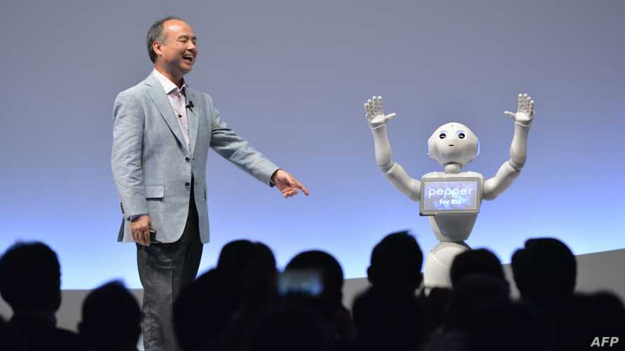 SoftBank Group representative Masayoshi Son and humanoid robot Pepper deliver a presentation at the SoftBank World 2015 in Tokyo on July 30, 2015. The two-day event for enterprise customers held special sessions given by SoftBank management and guest