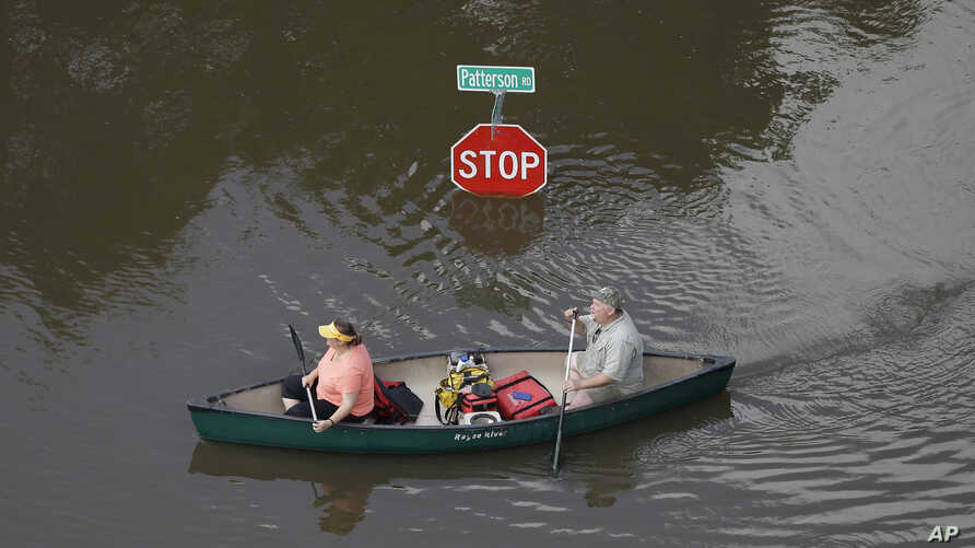 People canoe through floodwaters past a stop sign near Bear Creek Park in Houston, May 30, 2015.