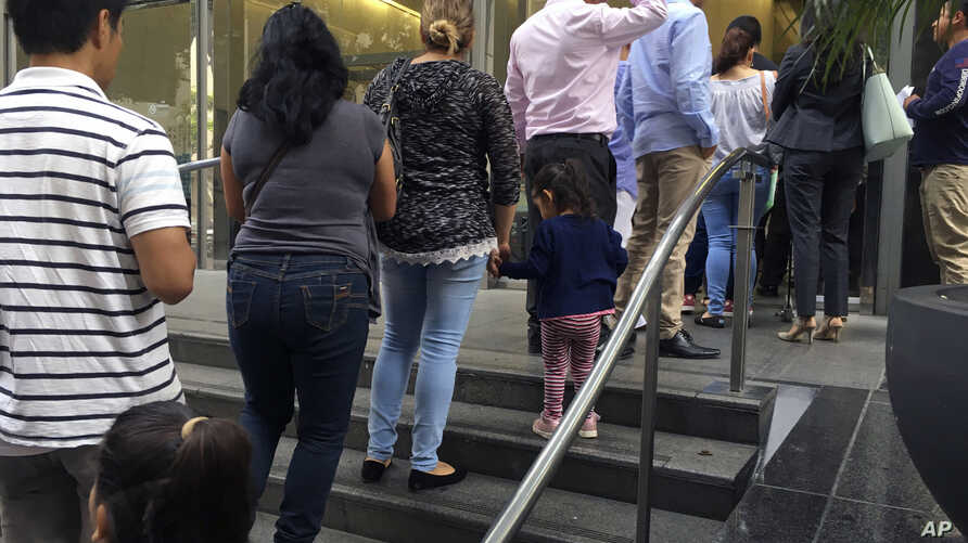 FILE - People line up outside the building that houses the immigration courts in Los Angeles, June 28, 2018.