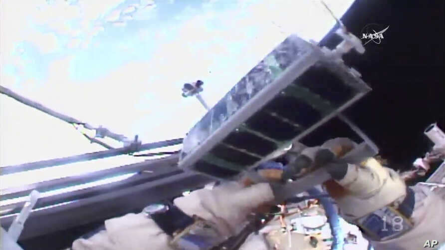 In this image made from video provided by NASA, Russian cosmonaut Sergey Ryazanskiy holds a small satellite before launching it by hand from the International Space Station, Aug. 17, 2017.
