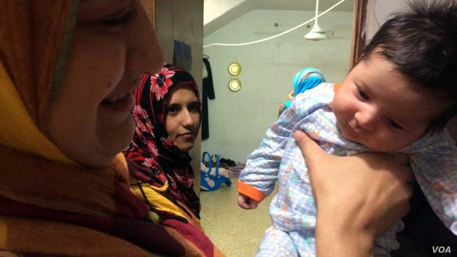 Dhoa, seen here with her 2-year-old baby, is torn on the issue, saying she wants both the choice to wear or not to wear a veil and the safety that comes with the military's ability to identify IS militants hiding among them in Mosul, Iraq, June 8, 20