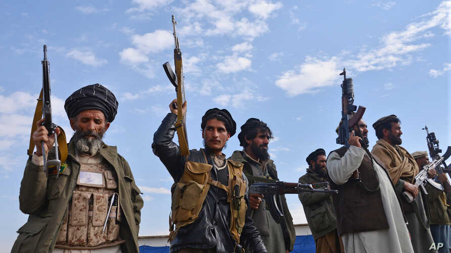 FILE - Afghan militia men raise their weapons as they stand guard in the Achin district of Nangarhar province east of Kabul, Afghanistan, Dec. 27, 2015.