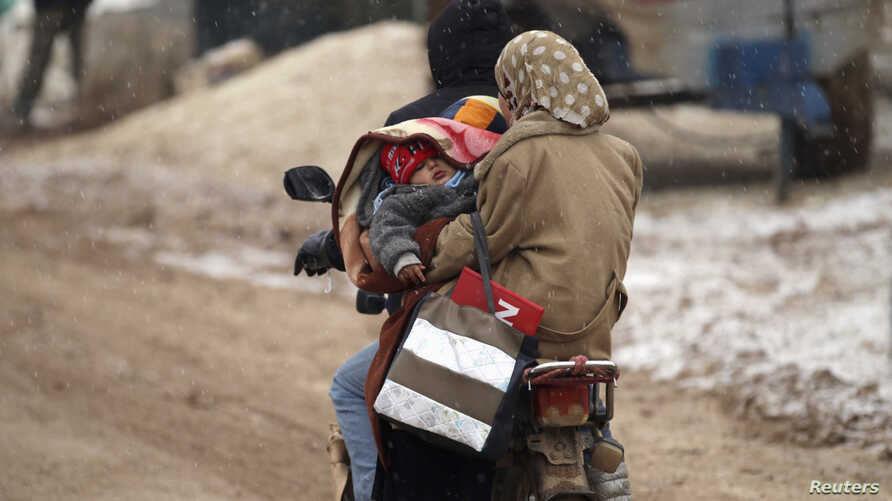 FILE - Internally displaced refugees carry a baby on a motorcycle during a snow storm inside Salkeen refugee camp, Northern Idlib countryside,  Jan. 10, 2015.