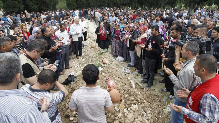 People mourn at the grave of a dead miner after the burial service in a cemetery in Soma, a district in Turkey's western province of Manisa May 15, 2014. Loudspeakers broadcast the names of the dead and excavators dug mass graves in this close-knit T